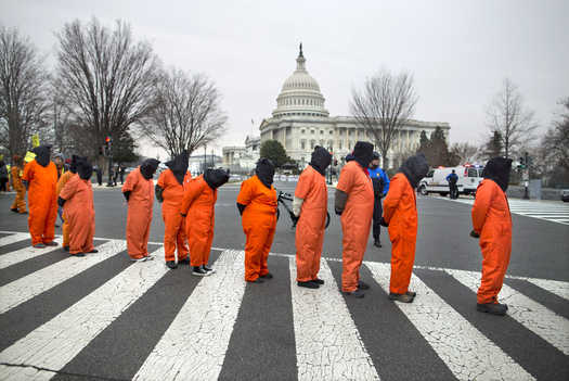 Demonstrators dressed as detainees march past the Capitol building